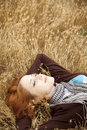 Young beautiful girl lying at yellow autumn field. Royalty Free Stock Photos