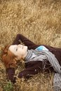 Young beautiful girl lying at yellow autumn field. Royalty Free Stock Image
