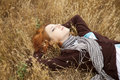 Young beautiful girl lying at yellow autumn field. Royalty Free Stock Images