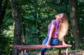 Young beautiful girl model in jeans and a T-shirt with long blond hair and sad smiles pensively posing for a walk in the autumn pa