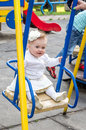 Young beautiful girl mother rolls her daughter with a bow on her head which is show your laughing two teeth on a swing in amuseme Royalty Free Stock Photo