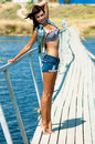 Young beautiful girl on the pier at the river in denim shorts Stock Images