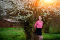 Young beautiful girl in a pink shirt standing under blossoming apple tree and enjoying a sunny day. Royalty Free Stock Photo