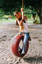 Young beautiful Girl Playing On Tire Swing In the farm Royalty Free Stock Photo