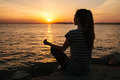 Young beautiful girl practicing yoga and meditation on the rocks next to the sea at sunset. Sport. Yoga. Meditation Royalty Free Stock Photo