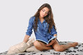 Young beautiful girl reading a book in denim shirt on the bed Royalty Free Stock Photos