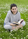 Young beautiful girl reads book in a park Stock Photo