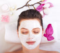 Young beautiful girl receiving pink facial mask spa beauty salon Stock Photography