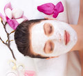 Young beautiful girl receiving pink facial mask spa beauty salon Stock Image