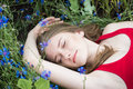 Young beautiful girl relaxing in the meadow of cornflowers