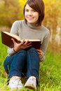 Young beautiful girl sits on bridge and reads book Royalty Free Stock Photography