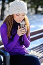 Young beautiful girl sitting on the bench in winter forest Stock Photography