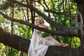 Young beautiful girl sitting on a big tree in summer park Royalty Free Stock Photo
