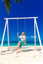 Young beautiful girl sitting on a swing under a palm tree blue tropical sea in the background Stock Image