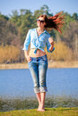 Young beautiful girl in spring slender woman with bare belly and feet standing at the lake early Stock Photos