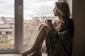 Young beautiful girl student sitting on a window sill at the window overlooking the city and drinking hot coffee from a mug Royalty Free Stock Photo