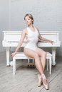 Young beautiful girl in white dance leotard and Pointe shoes, ballet dancer. Sits, background piano, style, grace Royalty Free Stock Photo