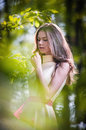 Young beautiful girl in a yellow dress in the woods. Portrait of romantic woman in fairy forest. Stunning fashionable teenager Royalty Free Stock Photo