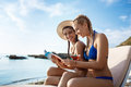 Young beautiful girls in swimwear smiling, browse magazine  at seaside. Royalty Free Stock Photo