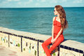 Young beautiful glam stylish woman wearing coral red jumpsuit and dark trendy sunglasses sitting on the parapet at the seaside Royalty Free Stock Photo