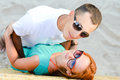 Young beautiful happy couple embracing on sandy beach outdoors Royalty Free Stock Photos