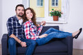 Young beautiful happy couple sitting on sofa in living room portrait of Royalty Free Stock Photo