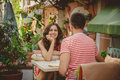Young beautiful happy loving couple sitting at street open-air cafe looking at each other. Beginning of love story. Relationship Royalty Free Stock Photo