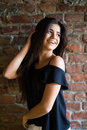 Young beautiful happy woman in casual clothes against brick wall