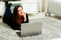 Young beautiful happy woman lying on the floor with laptop at home Stock Photos