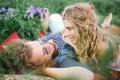 Young beautiful hippie couple lying on grass having fun