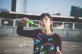 Young beautiful hipster woman bubble blower in the city Royalty Free Stock Photo