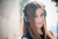 Young beautiful hipster woman listening music to with headphones in the city Royalty Free Stock Photography