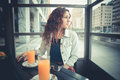 Young beautiful hipster woman with red curly hair at the bar Royalty Free Stock Image