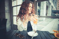 Young beautiful hipster woman with red curly hair at the bar Stock Photo