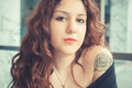 Young beautiful hipster woman with red curly hair at the bar Royalty Free Stock Photography