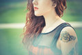 Young beautiful hipster woman with red curly hair in the city Stock Photo