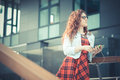 Young beautiful hipster woman with red curly hair listening music in the city Royalty Free Stock Image