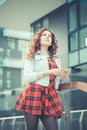 Young beautiful hipster woman with red curly hair listening music in the city Royalty Free Stock Images