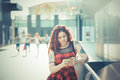 Young beautiful hipster woman with red curly hair listening music in the city Royalty Free Stock Photo