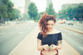 Young beautiful hipster woman with red curly hair listening music in the city Stock Photos
