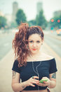 Young beautiful hipster woman with red curly hair listening music in the city Stock Photo
