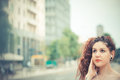 Young beautiful hipster woman with red curly hair listening music in the city Stock Images