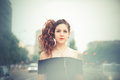 Young beautiful hipster woman with red curly hair listening music in the city Royalty Free Stock Photography