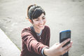Young beautiful hipster woman using smart phone selfie in the city Royalty Free Stock Image