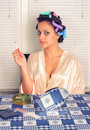 Young beautiful housewife smoking cigarette with curlers in her hair in the kitchen Stock Photo