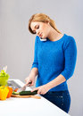 Young and beautiful housewife woman cooking in a kitchen the is also talking on the phone Royalty Free Stock Images
