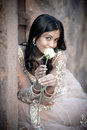 Young beautiful indian woman sitting against stone wall outdoors with single white rose Royalty Free Stock Photos