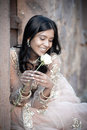 Young beautiful indian woman sitting against stone wall outdoors smiling with single white rose Royalty Free Stock Photos
