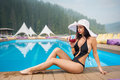 Young beautiful lady in a hat and black bikini sitting next to swimming pool and drinking cocktail