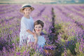 Young beautiful lady mother with lovely daughter walking on the lavender field on a weekend day in wonderful dresses and hats. Royalty Free Stock Photo